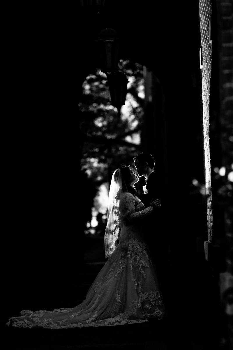 Dramatic backlighting frame a bride and groom kissing in a brick archway in Harvard University