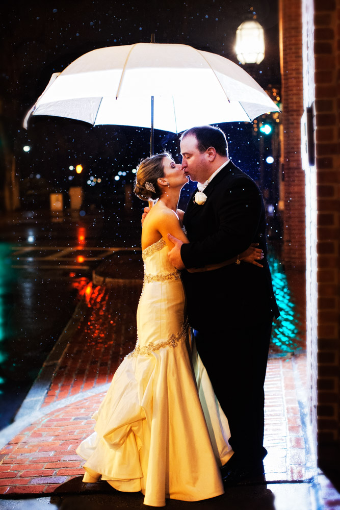A bride and groom kiss in the rain under an umbrella with rain drops illuminated from the city lights at night.