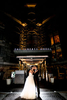 A bride and groom pose together in front of the Liberty Hotel at night with dramatic lighting.
