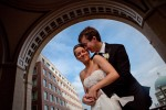 A bride and groom embrace at the famous archway of the Harbor Hotel with a beautiful blue sky during their summer wedding