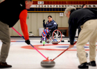 In the role as skip, Meghan Lino, 29, of  East Falmouth directs her teammates David Nisula of Cotuit, left, and John Howard of Falmouth as they sweep during a match at the Cape Cod Curling Club. Lino will compete in the Paralympic games in Sochi.
