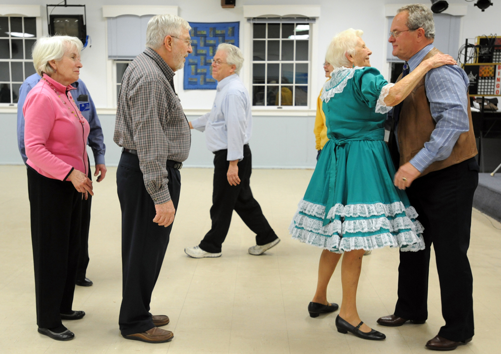 Vida Demale of Eastham hugs the caller Jim Shell of Lakeville as others lineup to thank him and bid him goodnight after an evening to fellowship. According to square dance etiquette, it's important to line up and formally show gratitude to the caller at the end of the night.
