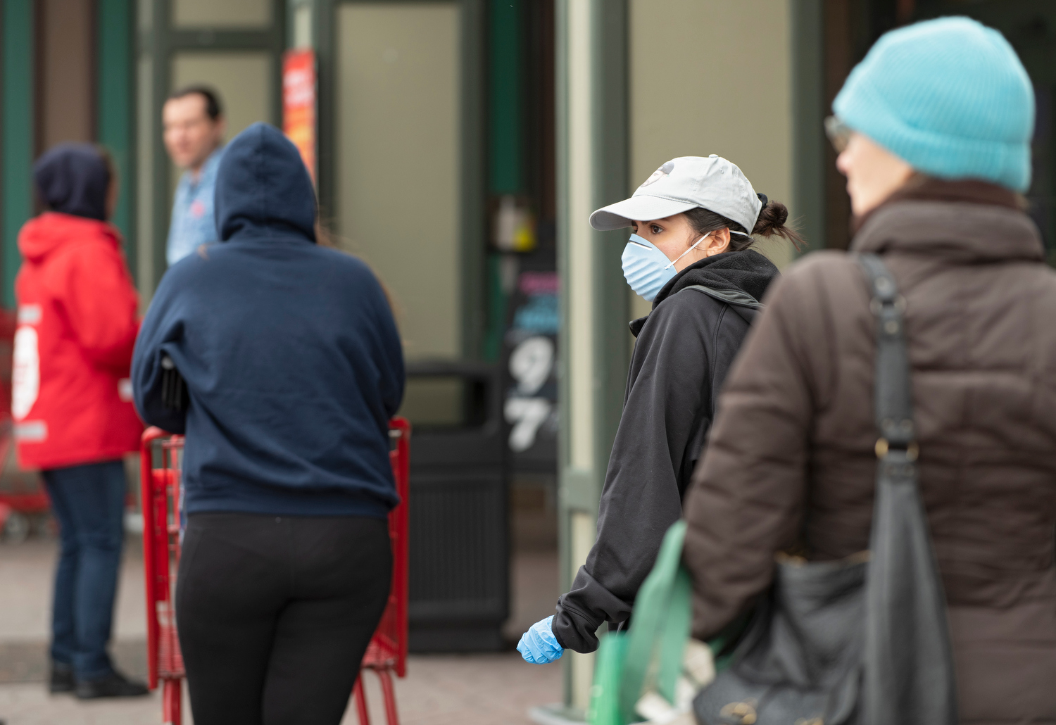 HYANNIS - A shopper wearing a mask waits to get in to Trader Joe's on Monday, March 23, 2020. The store was limiting the number of customers  allowed to be in the store.