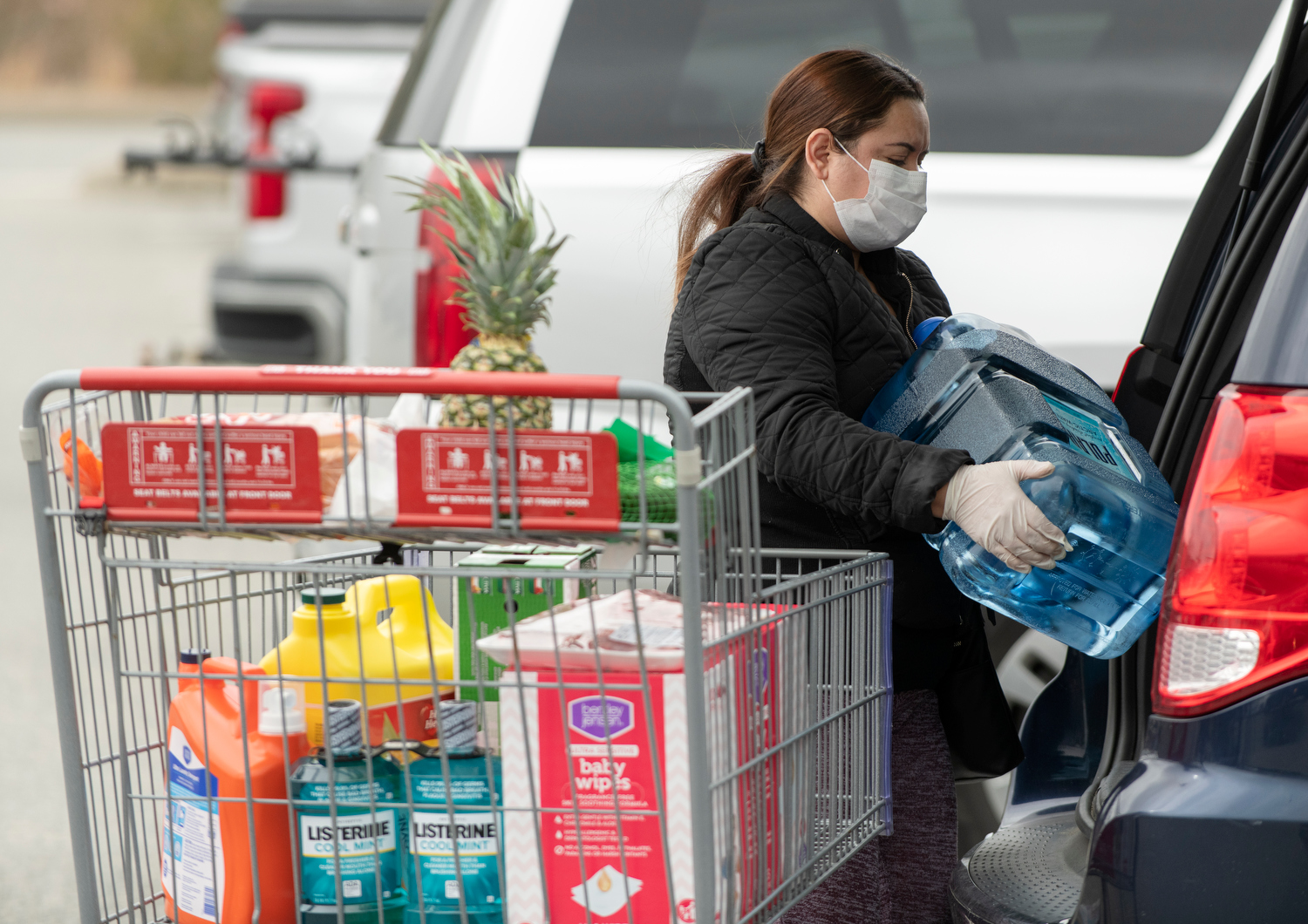 HYANNIS - A masked shopper loads up her minivan with supplies in the BJ's Superstore parking lot on Monday, March 23, 2020.