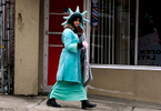 Yachira Dejesus, 22, dressed as the Statue of Liberty, walks past Sena's Cutting and Styling reminding passers-by that tax season is upon them on Friday, March 27, 2015.