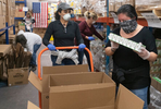 JOINT BASE CAPE COD - Volunteers Corrine Wickel, left, and Jennifer Wisse, pack boxes with a 14-day supply of food for veterans and their families on Thursday, April 2, 2020. This Food4Vets initiative is organized by the Massachusetts and Cape Cod Military Support Foundations and has a goal of distributing 50,000 boxes.