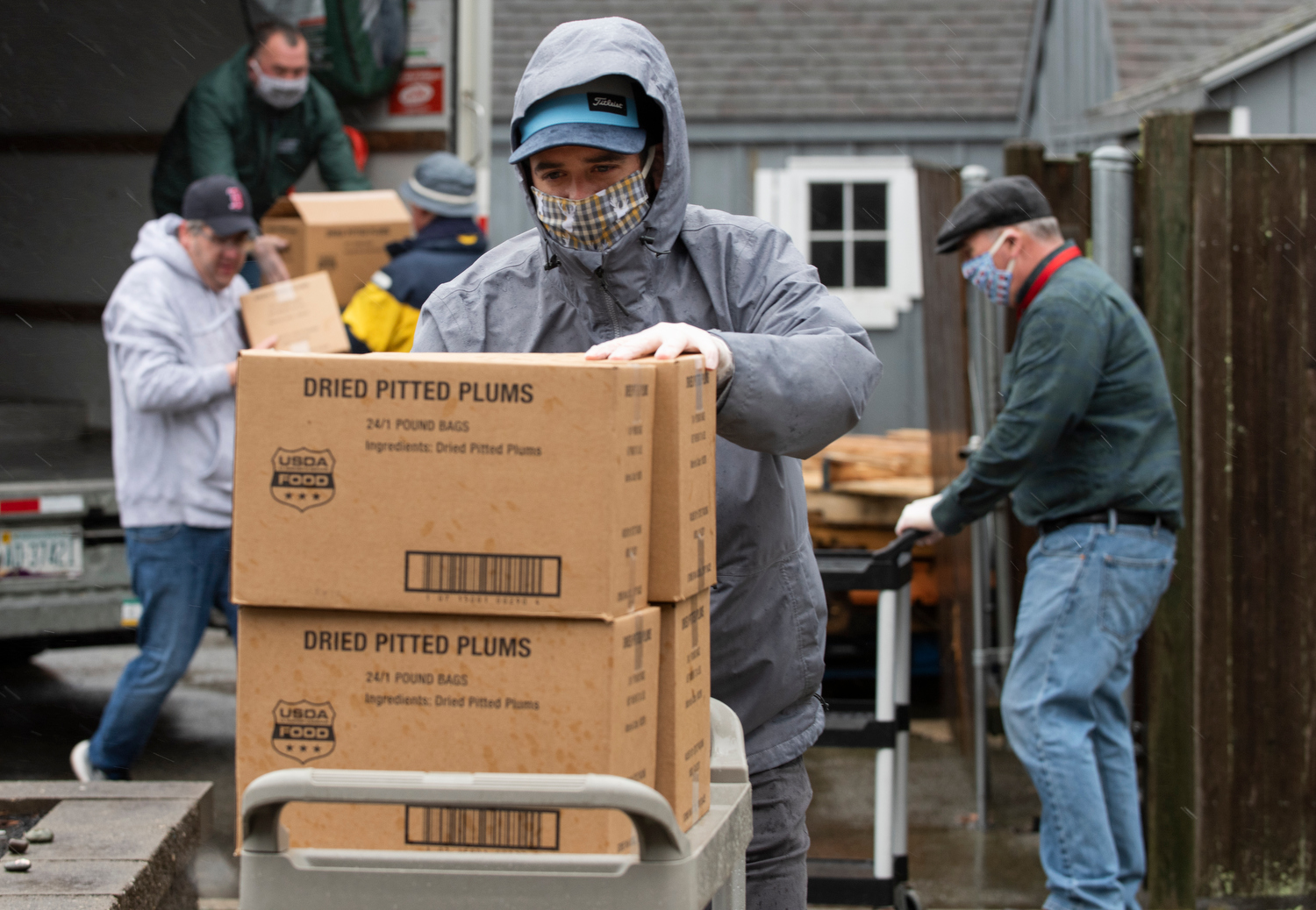 HYANNIS - Town golf course employees brave the wind and rain to bring in a food delivery to the Adult Community Center on Friday, April 3, 2020. The crew was tasked with putting together 240 bags of food to be delivered to seniors.