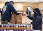 HYANNIS - Kris Clark, Barnstable town councilor, hands canned goods to James Bentley, assistant superintendent of Barnstable's golf operations, on Friday, April 3, 2020. The crew was tasked with putting together 240 bags of food to be delivered to seniors.