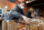 YARMOUTH PORT - Steve Dalin and Kathy Kuck place cookies baked by the Hyannis Garden Club in bagged lunched for the homeless at Harvest of Cape Cod. Store owner Pamela Parker has temporarily closed her home decor retail store because of Gov. Baker's shutdown of {quote}nonessential{quote} businesses. She's still open online but in the midst of all this uncertainty, she decided to make space in her warehouse to put together these meals since there is a gap in meal services for the food insecure on the weekend. She and her employees have put together over a hundred bagged meals and dropped them off at Saint Joseph House shelter in Hyannis.