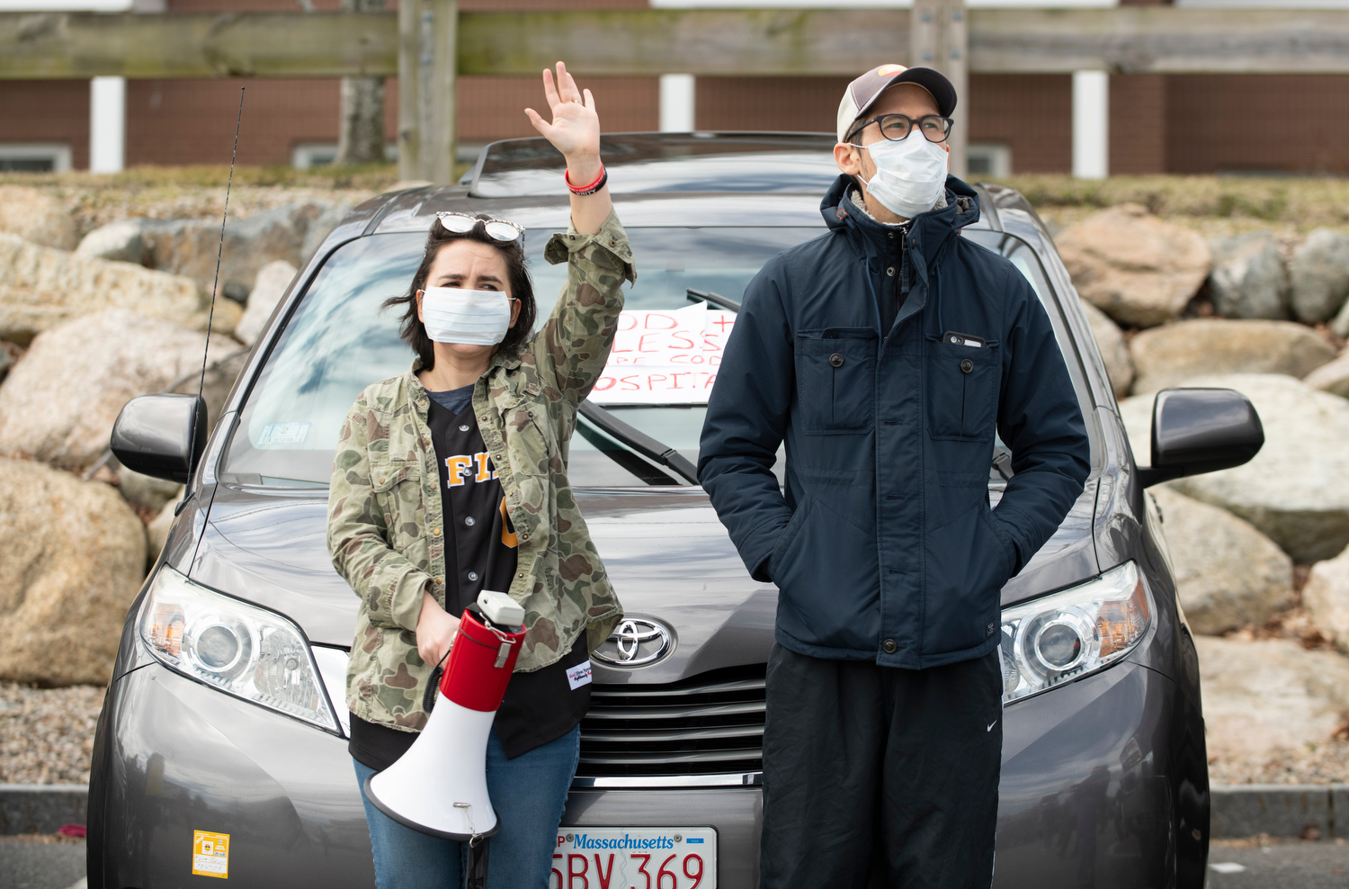 HYANNIS - Organizer Inna Taylor, youth director at Grace Church, and her husband Andrew Taylor wave to healthcare works from the Cape Cod Hospital parking lot on Friday, April 10, 2020.