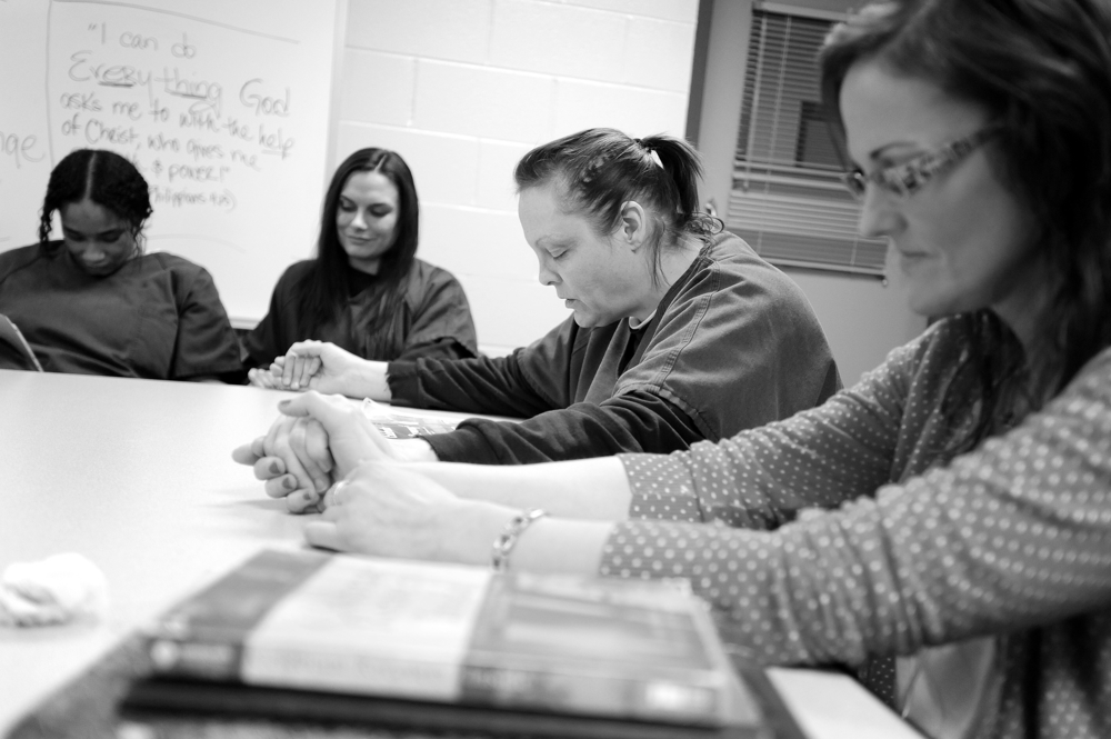 Barnstable County Correctional Facility inmate Desiree Azarian prays with with Celebrate Recovery facilitator Susy McAlvin, far right, with fellow inmates Tyashia Warren, far left, and Jessica Cardinal.