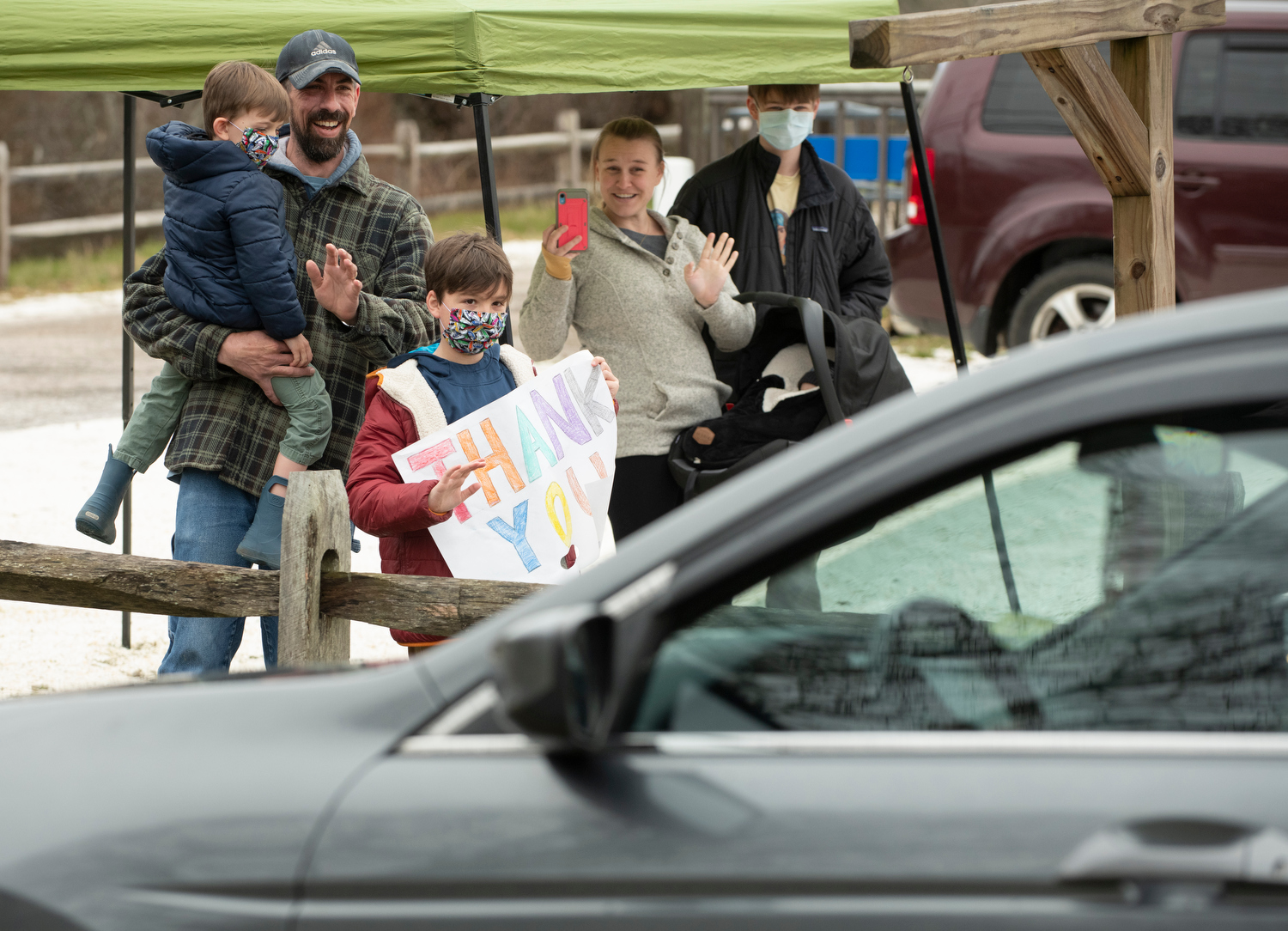 """TRURO - Cameron Miner, 9, receives birthday greetings in the form of a """"Birthday Caravan"""" organized by Truro's Recreation Department on Wednesday, April 15, 2020. His parents, Chris and Nicole and brother, Gus, 4, wave to the well-wishers behind him."""