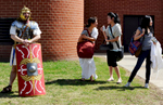 Andy Volpe of Worcester, dressed as a first century Roman, awaits the stat of the Holy Cross annual Classics Day chariot race as Belmont High School students Bonnie Jin, 15, Amelia Rasmusen, 16, and Jia Zhang, 15 socialize on Thursday, April 16, 2015.