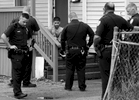 Police talk with a man at 12 Clapp Street where shots were fired according to scanner reports on Friday, April 17, 2015. The man was later taken by ambulance with an apparent head injury.