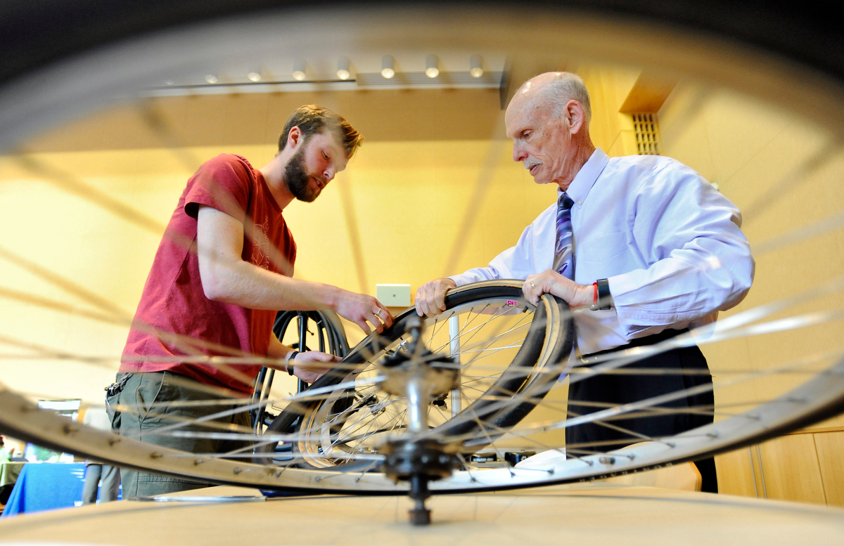 Worcester Earn a Bike volunteer Matt Warndorf, left, shows Dr. Joel Gore how to fix a flat during the 10th annual Earth Day celebration at UMASS Medical School on Wednesday, April 22, 2015. Gore said he wanted to learn because his wife always fixes his flats.