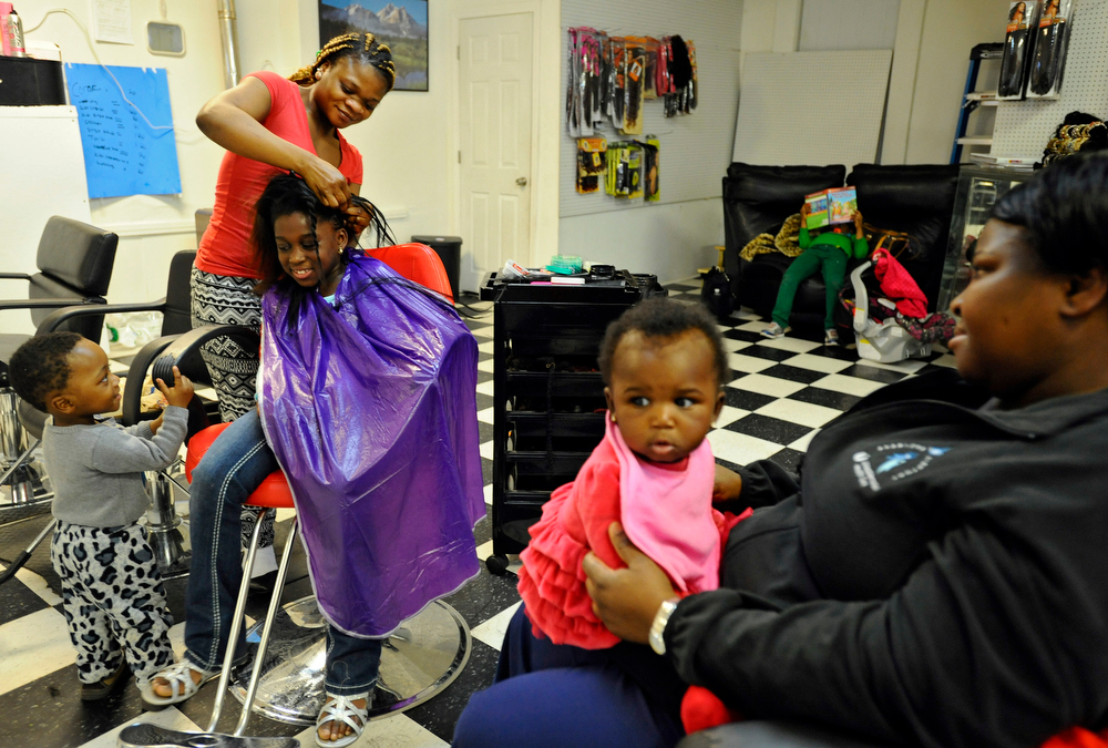 Evelyn Gray gives Audrey Nortey, 8, some corn rows with her son, Daniel Frempong, 1, at her side as Harriet Nortey and her daughter, Joelle, 8 months, watch at Evelyn's Braiding Shop on Thursday, April 23, 2015.