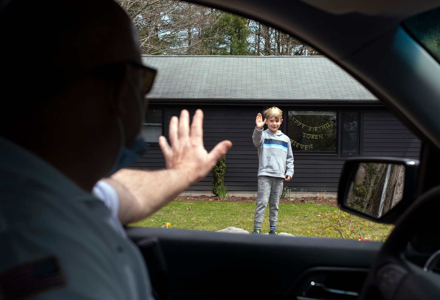 C.O.M.M. Fire District Captain Chris Adams waves to Soren Wake, 7, while participating in a birthday parade of emergency vehicles on Wednesday, May 6, 2020.