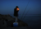 8:15 p.m. -- Chris Carey of Pembroke fishes for stripers on the Scusset Beach jetty on Tuesday, August 19, 2014. He said he would stay out there until 4 or 5 a.m. {quote}The excitement of actually catching a fish. You don't know how big it's gonna be or how good it is until you catch it and pull it in,{quote} he said of why he stay outs all night. {quote}You've got to put your time in. I've taken a nap before and gotten chowed by mosquitoes, a little breeze helps.{quote} He added that he smokes cigarettes to keep the pests away since he doesn't like bug spray.