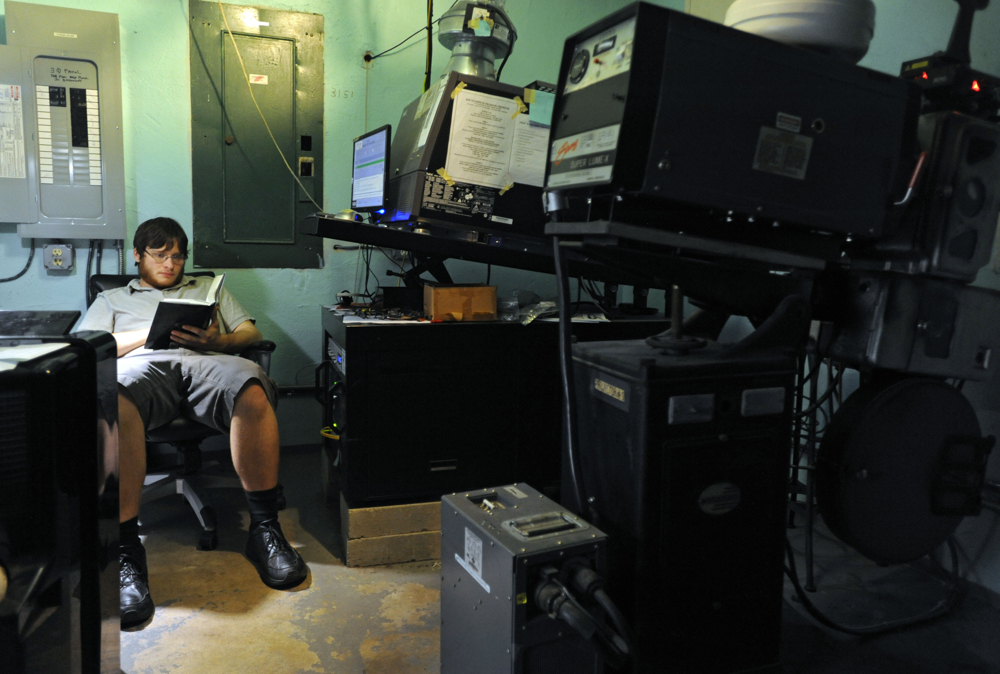 9:03 p.m. -- Framed by a reel projector on the right, Cape Cod Cinema projectionist Dan Neal reads a book while showing the Woody Allen film {quote}Magic in the Moonlight{quote} with a digital projector on Wednesday, August 27, 2014.