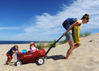 Ronan Laplante, 4, tries to help his mother, Brooke, as she pulls her daughter, Nora, 8 months, and their beach gear in a wagon up the dune returning from a day at Truro's Coast Guard Beach on Wednesday, September 3, 2014.