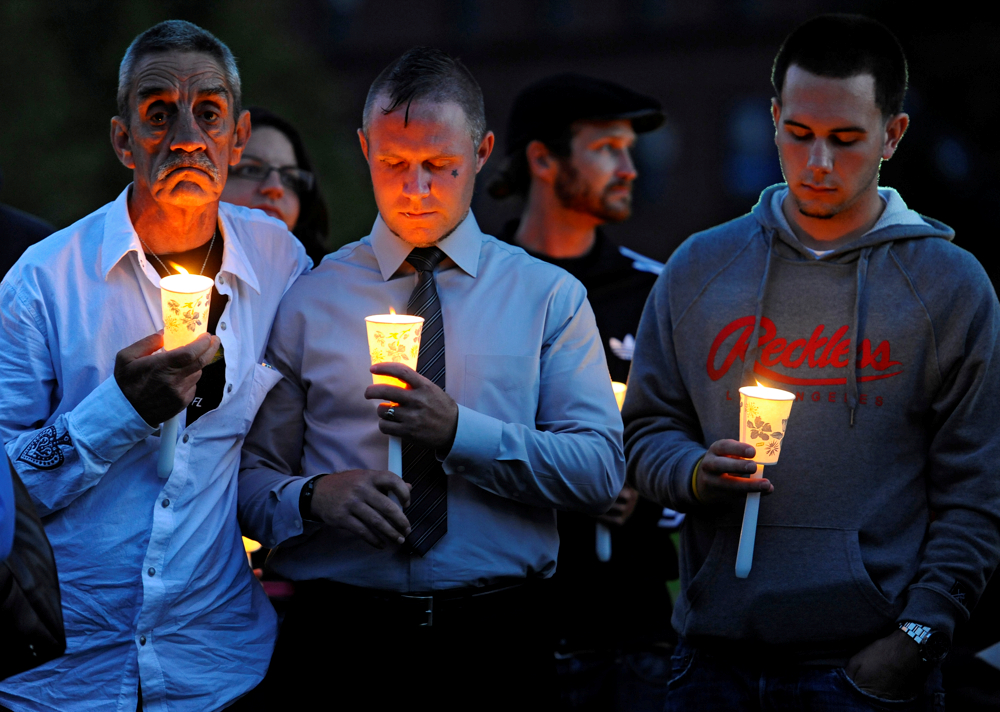 From left, Raymond Bastille of Falmouth, Kristoph Pydynkowski of Buzzards Bay and Mike Tallia of Falmouth, who are all in recovery, hold candles during the third annual overdose vigil on the Hyannis Village Green on Sunday, September 22, 2014. Pydynkowski was the keynote speaker at the vigil. He shared his story of battling heroin addition. He is now an intervention and recovery specialist at Gosnold where he was treated.