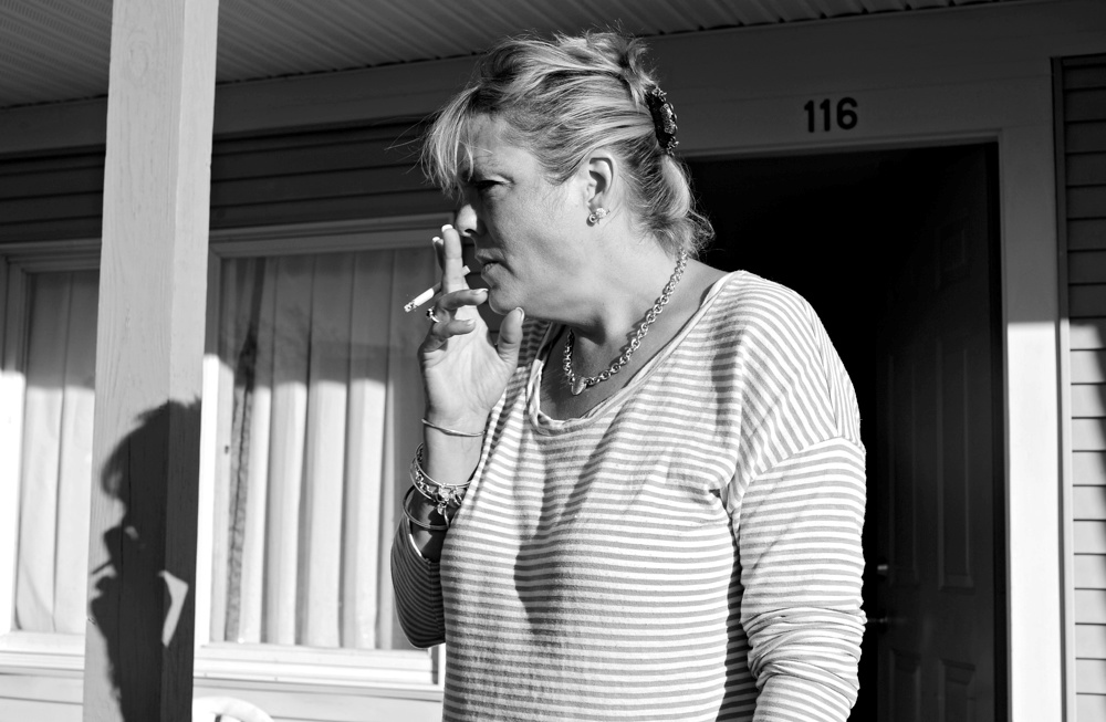 Desiree Azarian smokes a cigarette outside her friend's room at the Yankee Village Motel. She had relapsed back into drinking with him but after he went into diabetic shock the week before they both have vowed get sober again.