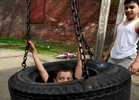 Elvin Cartagena, 5, of Worcester plays on a tire swing with Samuel Matias, 11, behind an apartment building on King Street on Tuesday, May 5, 2015. T&G Staff/Christine Hochkeppel