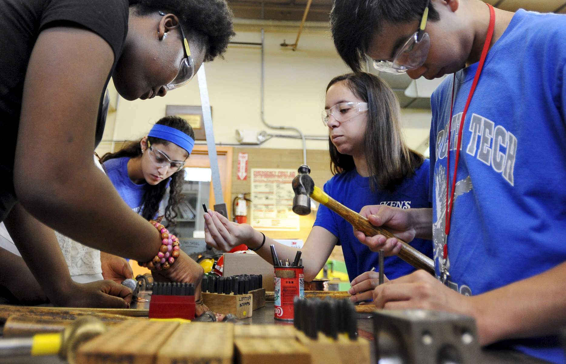 Worcester high school students Emmanuella Amoah, 5, left, and Hoang Vo, 15, work on hammering designs into copper bracelets during the STEM initiative jewelry-making class at the Worcester Center for Crafts on Wednesday, July 15, 2015.