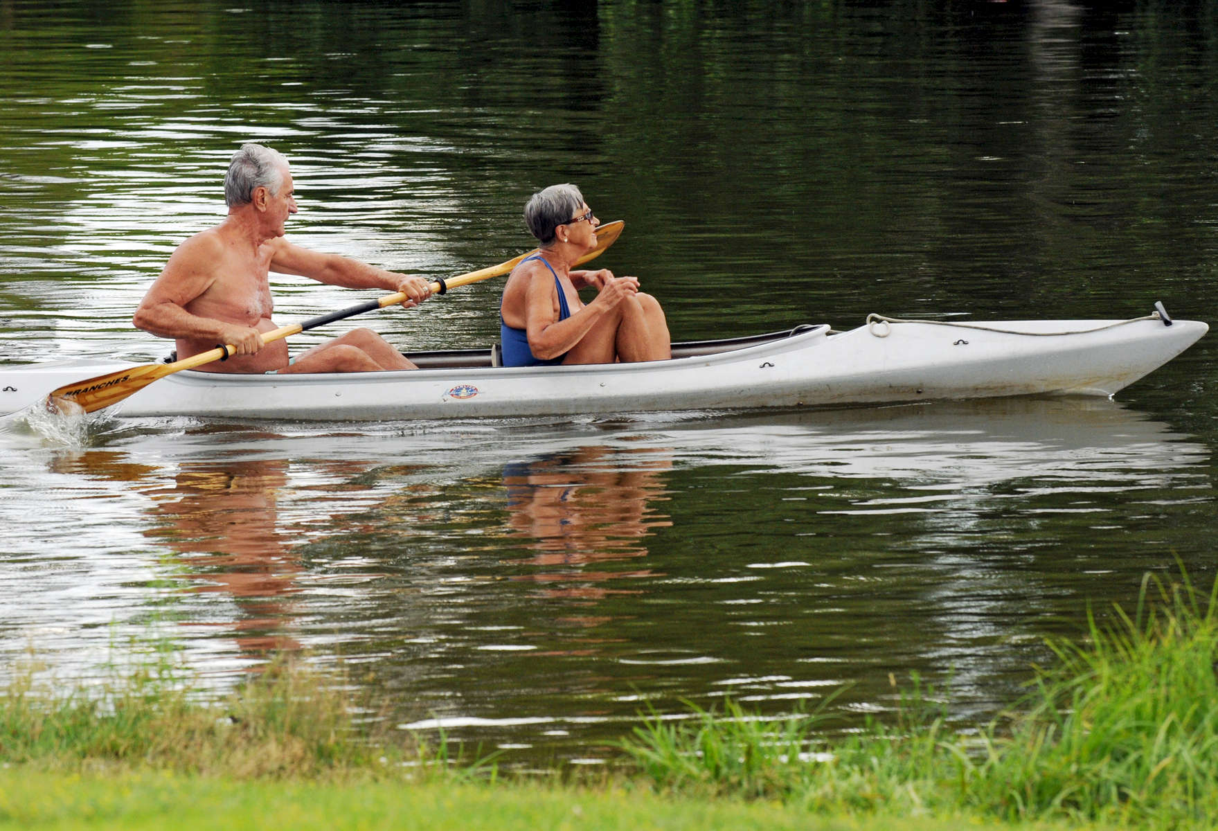 Francis and Ildi Kovago kayak on Indian Lake just as the rain clouds roll in on Wednesday, July 15, 2015. The couple said they used to teach sailing lessons on the lake but on a calm day like today, kayaking is best. T&G Staff/Christine Hochkeppel