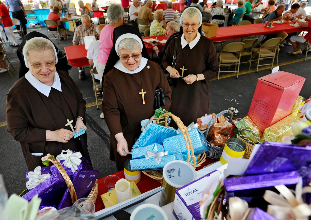 From left, Sisters Jeanne Marie Akalski, Mary Valenta Akalski and Mary Ann Papiez of St. Joseph's Basilica place their raffle tickets on the prizes that interest them at the St. Andrew Bobola Church Festival on Saturday, August 29, 2015.