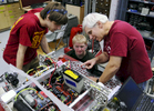 Robotics instructor Brad Miller, right, works with WPI mentors Logan Tutt, 20, far left, and Nick Gigliotti in making the final adjustments to Team 190's robot, {quote}Goat-Goat,{quote} on Tuesday, Feb. 23, 2016. The team, a collaboration of Mass Academy and WPI, will compete in the FIRST Robotics Competition.