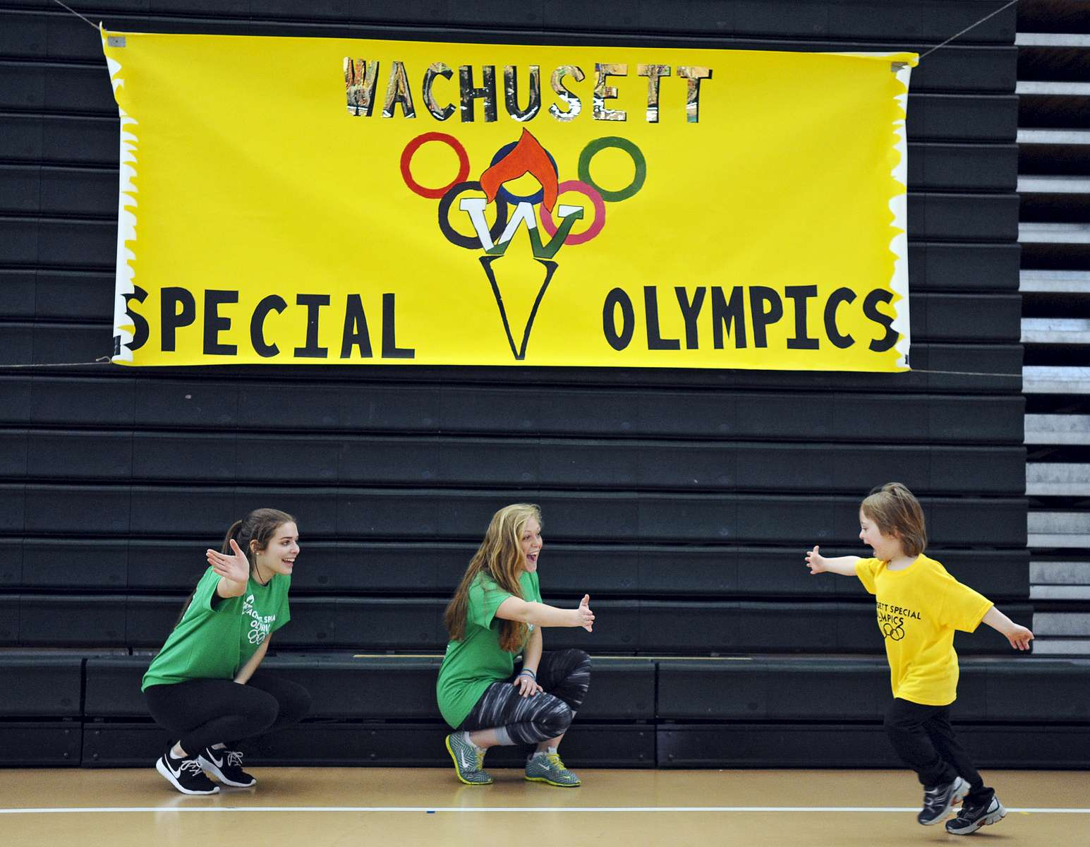 Jacob Reando, 5, of Paxton collects high fives from Wachusett High School freshman Maddie Wilde, 15, and junior Alexis Bergman, 17, far left, during the 3rd annual Wachusett Special Olympics on Thursday, March 17, 2016. T&G Staff/Christine Hochkeppel