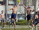 Becker College students Eli Lynn and Trey Kerns reach for the disc during a game of Ultimate Frisbee with their fellow ice hockey teammates at Elm Park on Wednesday, April 20, 2016.