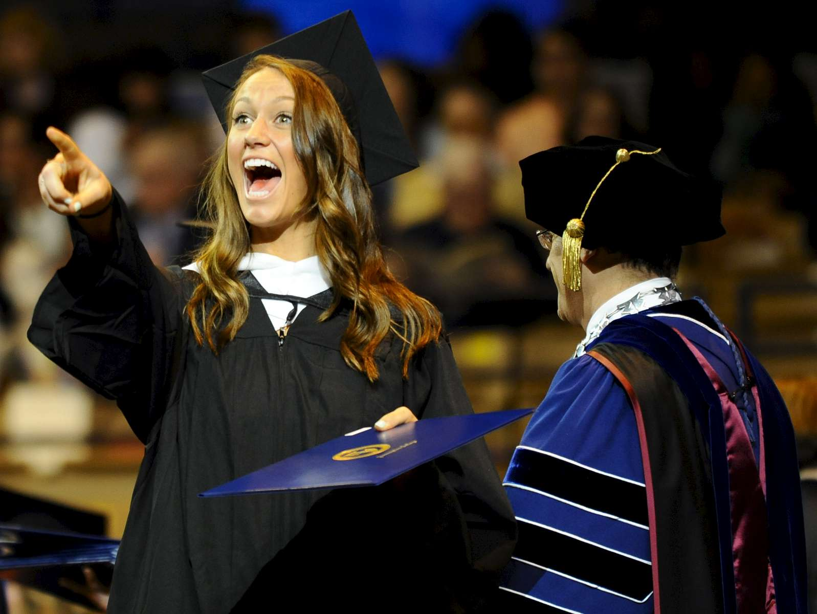 Assumption College graduate Meghan Campbell excitedly gestures to a loved one after receiving her diploma on Saturday, May 7, 2016.