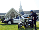 Auburn police officer John MacLean polishes an Auburn motorcycle on display outside  St. Joseph's Church before the funeral for Auburn police officer Ronald Tarentino, Jr., 42, of Leicester at on Friday, May 27, 2016. Tarentino died after being shot in back during a traffic stop, his cruiser, number 6, is behind the motorcycle.