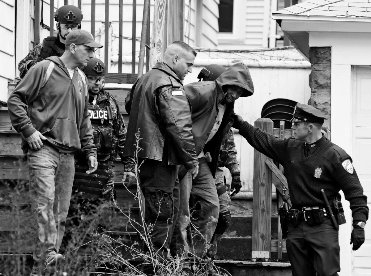 Worcester police officers escort a man who had barricaded himself in his residence at 25 Cargill Ave to an ambulance on Wednesday, Dec. 17, 2014.