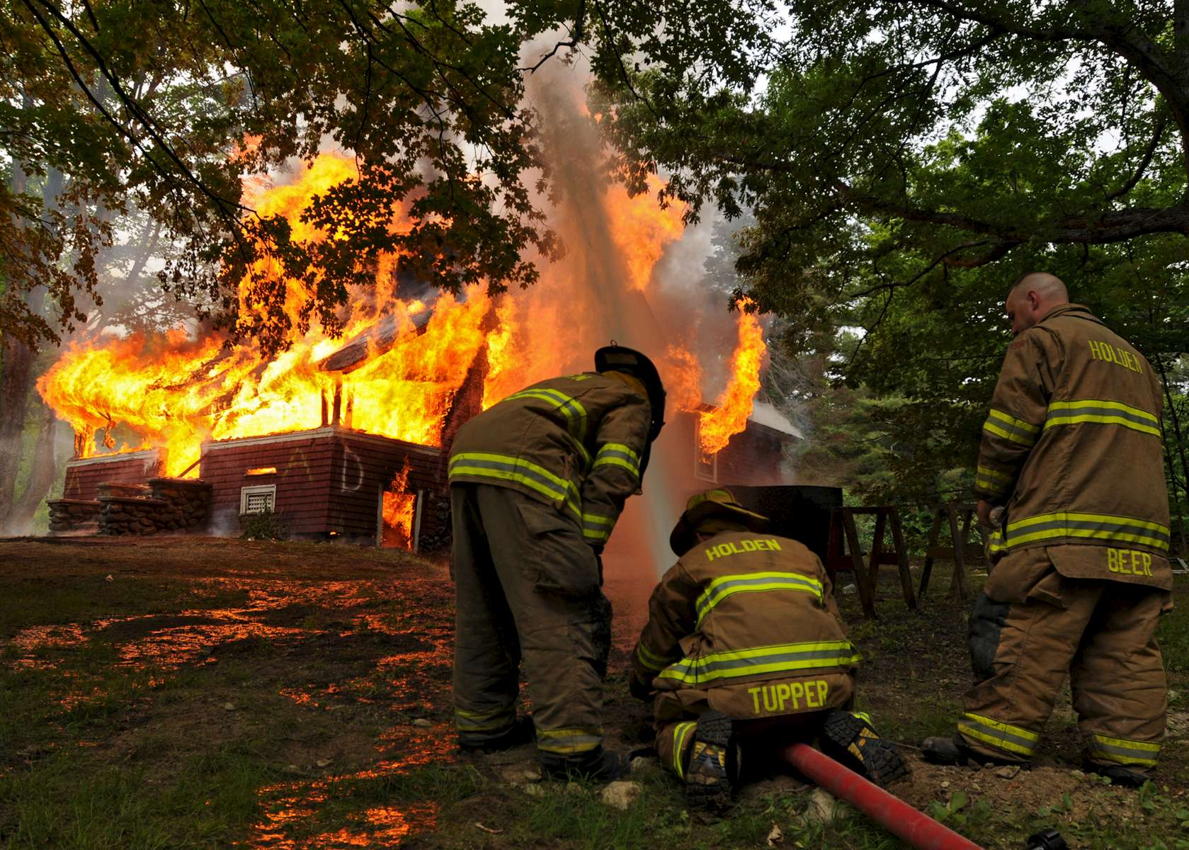 Holden firefighter Ryan Murphy, Lt. Barry Tupper and firefighter Bobby Beer man a nozzle while monitoring a controlled burn at the Creamer property at 175 Highland Street on Saturday, June 11, 2016.