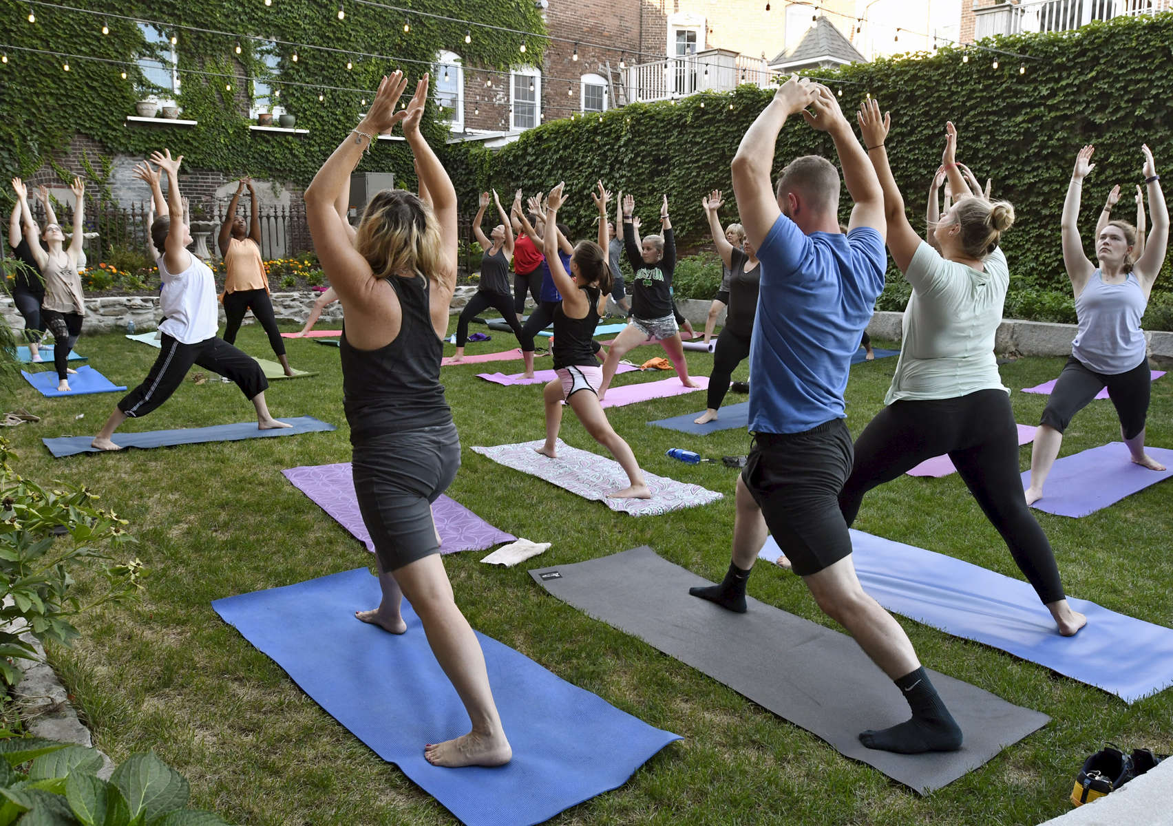 Flowforms Yoga instructor Polly Hensel leads a Hatha yoga class at Crompton Place on Thursday, August 4, 2016. Every Thursday in July and August, the studio offers a free outdoor class at 9pm in the courtyard.