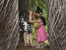Melanie Gnazzo of Worcester kisses her daughter, Carla Pacheco, 3, on the head as their explore Patrick Dougherty's {quote}Stick Work{quote} installation at Tower Hill Botanical Garden on Thursday, August 25, 2016.