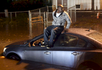 A man sits on the roof of his car waiting for help in the flood waters on Quinsigamond Ave on Friday, October 21, 2016.
