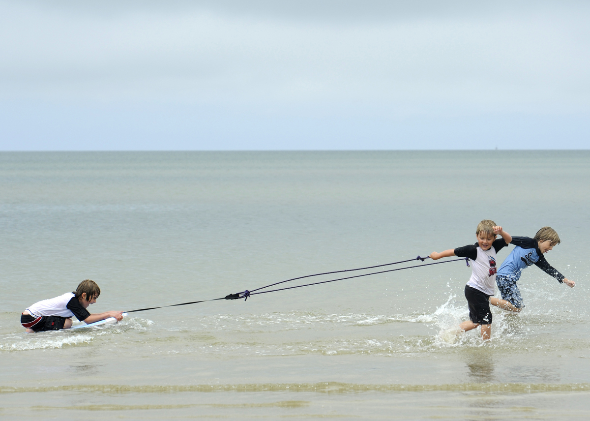 Brodie Hemingway, 5, and Max Bachand, 8,  pull Evan Hemingway, 7, at First Encounter Beach on Tuesday afternoon. The boys termed the activity {quote}belly boarding.{quote}