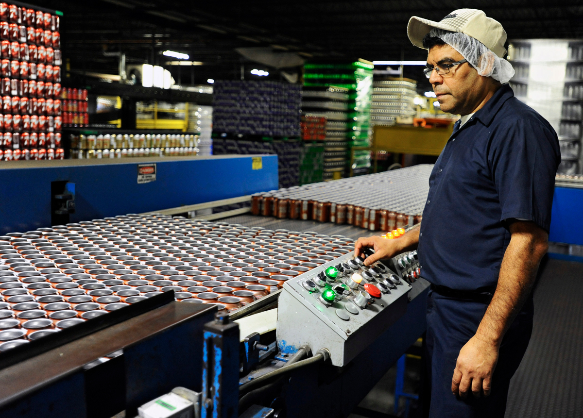 Production supervisor Carlos Flores, who was born in El Salvador, sorts cans in the Polar Beverages manufacturing plant © Christine Hochkeppel