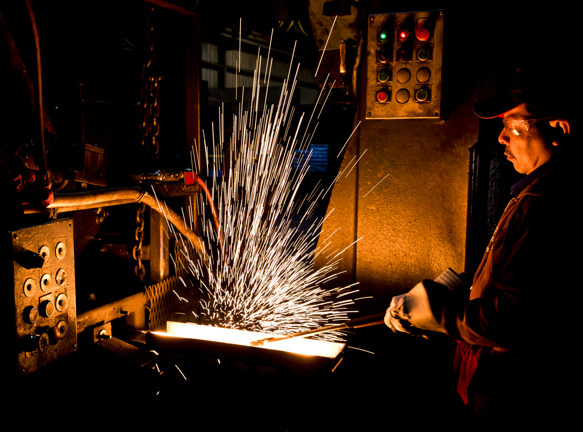 St. Pierre technician Juan Canas transfers a piece of steel into the forge press to form it into a horse shoe in the Worcester manufacturing plant.  © Christine Hochkeppel