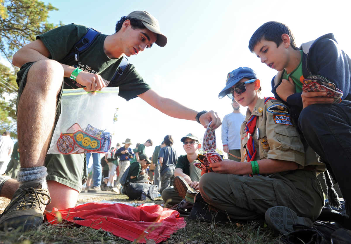 Michael Wheeler, 15, from Troop 38 of North Falmouth negotiates a trade of council shoulder patches for a deck of cards with Randall Scroggins, 13, and Ben Parsons, 12, both from Troop 256 of Plymouth, N.H. during the MassJam 2013 at Cape Cod Fairgrounds. © Christine Hochkeppel
