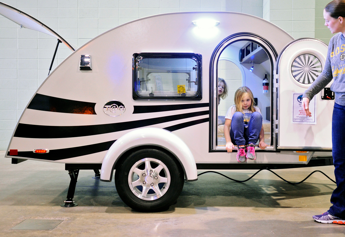 Sisters Aria, 3, and Emma, 5, emerge from {quote}The Little Guy{quote} at the urging of their mother, Jessica McCarthy of Fitchburg, during the RV & Camping Show at the DCU Center in Worcester. © Christine Hochkeppel