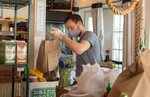PROVINCETOWN - Loic Rossignon, co-owner of the Canteen, a popular beachside cafe, prepares grocery orders for delivery and customer pickup on Tuesday, April 21, 2020. The restaurant normally only offers counter service and takeout but in response to the COVID-19 crisis Rossignon and his husband and co-owner, Rob Anderson, decided to not only to continue serving breakfast, lunch and prepared meals but to also sell groceries and cleaning products. They transformed their small dining area into a pantry and created an online ordering portal on their website. The business has received over $11,000 in donations to go toward free grocery orders for those who need assistance.