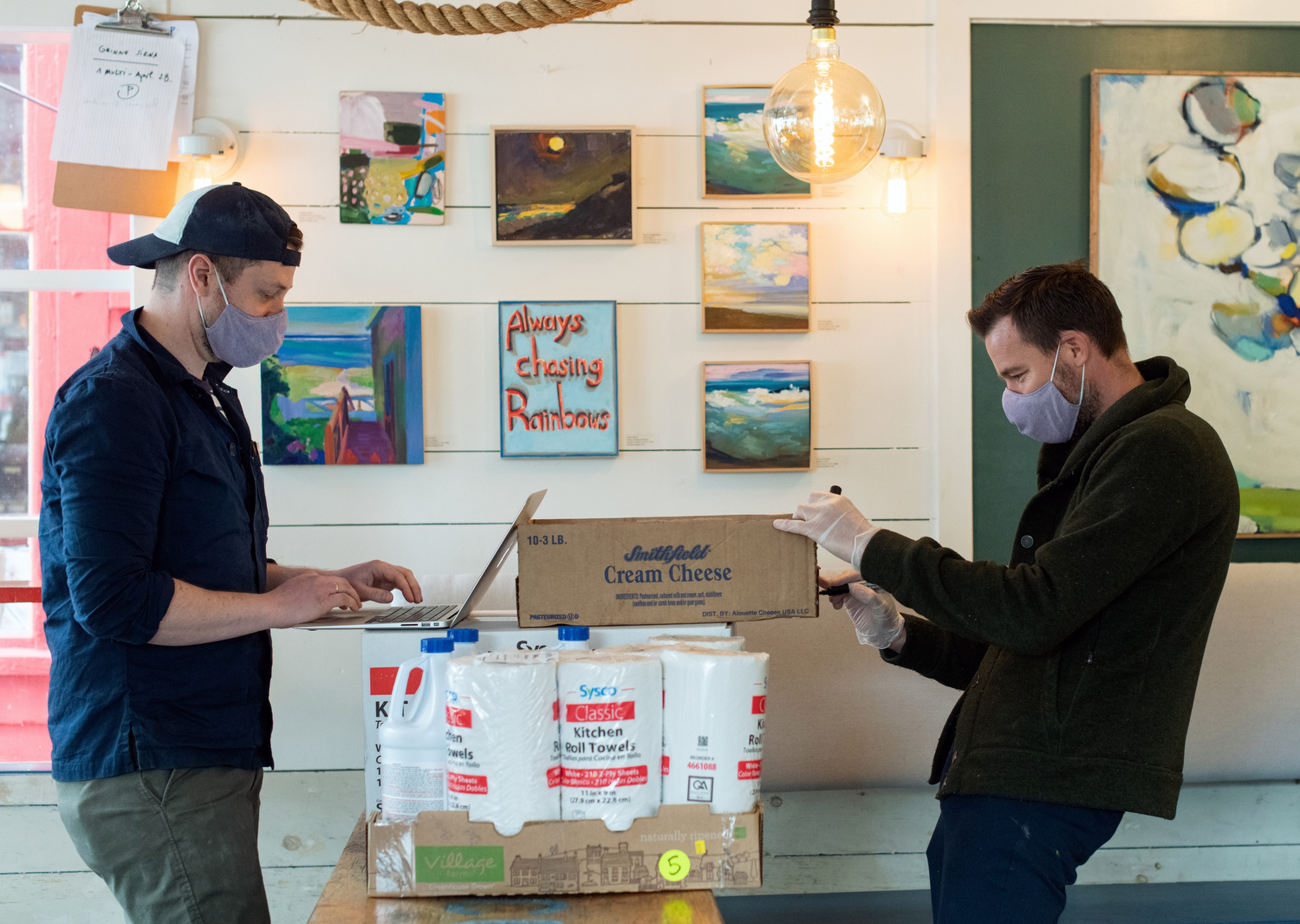 PROVINCETOWN - Rob Anderson, left, and Loic Rossignon co-owners of the Canteen, a popular beachside cafe, prepare grocery orders for delivery and customer pickup on Tuesday, April 21, 2020. Anderson and Rossignon have received over $11,000 in donations to go toward free grocery orders for those who need assistance.