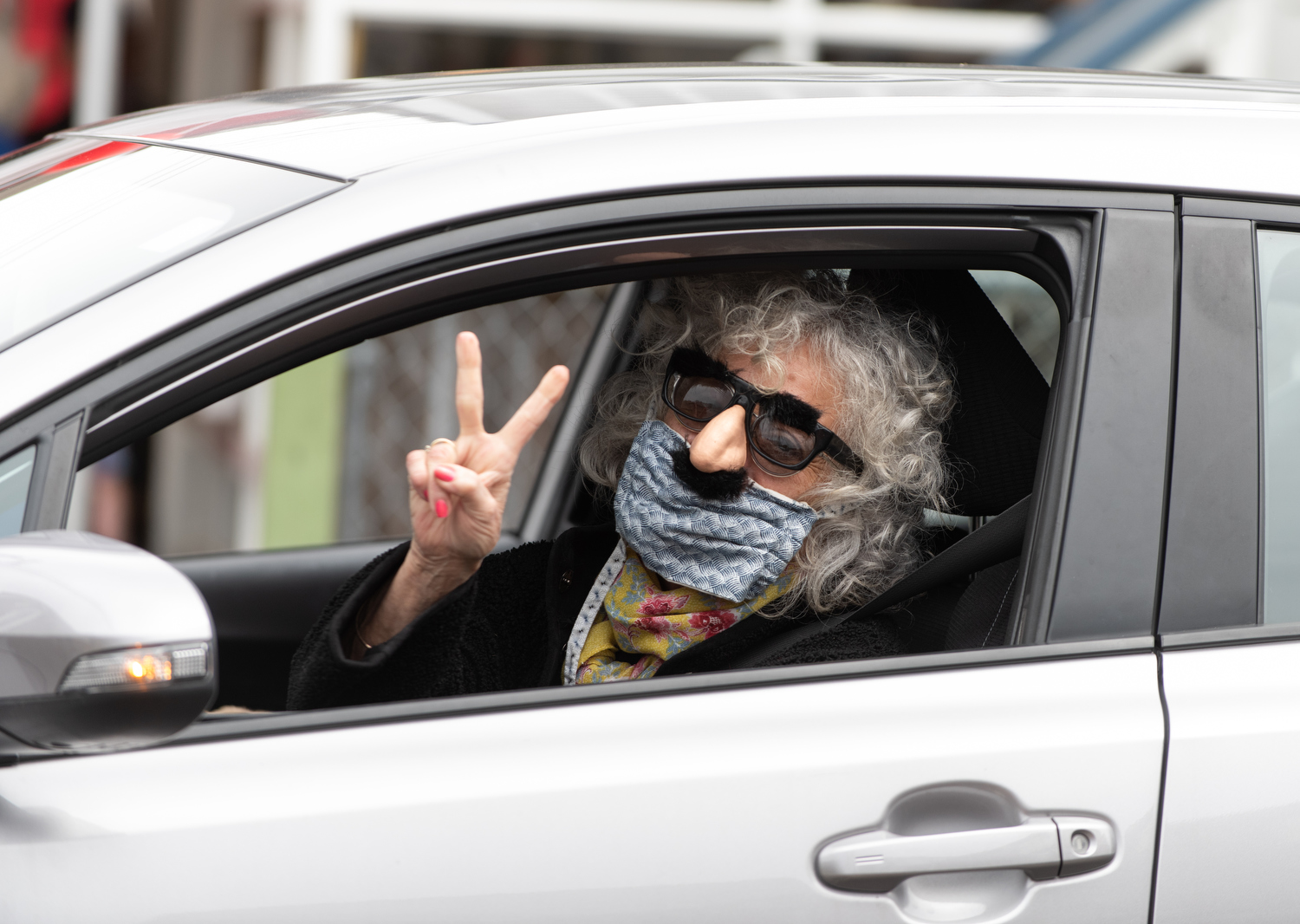 PROVINCETOWN - Canteen customer Corinne Sirna flashes a peace sign after picking up her grocery order on Tuesday, April 21, 2020. Anderson and Rossignon have received over $11,000 in donations to go toward free grocery orders for those who need assistance.