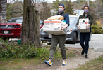 TRURO - Rob Anderson, front, and Loic Rossignon co-owners of the Canteen, a popular beachside cafe, deliver a free grocery order to a family living at the Truro Motor Inn, an unofficial and controversial affordable housing option for low-wage workers, on Tuesday, April 21, 2020. Anderson and Rossignon have received over $11,000 in donations to go toward free grocery orders for those who need assistance.