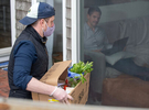 """PROVINCETOWN - Rob Anderson co-owner of the Canteen, a popular beachside cafe, delivers a grocery order to customer Javier Cortes on Tuesday, April 21, 2020. """"Through this process of being socially distant, we've become more intimate,"""" Anderson said of fulfilling his regulars grocery orders which then leads to """"quaint conversation."""""""